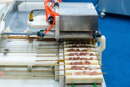 Close up asia barbecued or pork stick on support rail of automatic prick or stab pork machine for industrial manufacturing