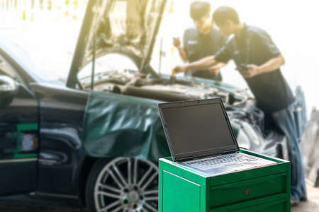 Close up laptop or computer notebook interfaced with car for repair during two repairman work investigate problem (program and electric check) automobile gasoline or diesel engine at garage