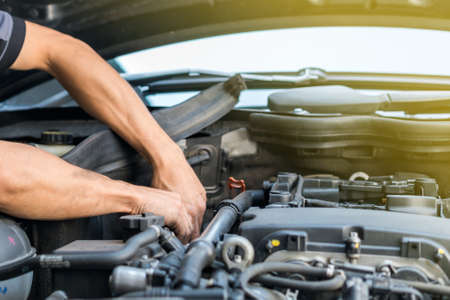 People or mechanic car repair during investigate cause of problem (mechanism check) or working on automobile gasoline or diesel engine at garage