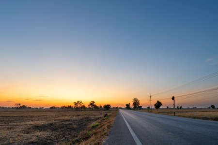 Golden beautiful Sunrise clear with dry grass fields and long asphalt road & electric pole in the countryside at morning on quiet day