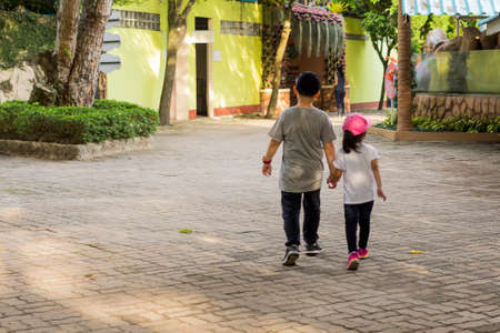 portrait of two kids brother and sister holding hands and walking on walkway in park