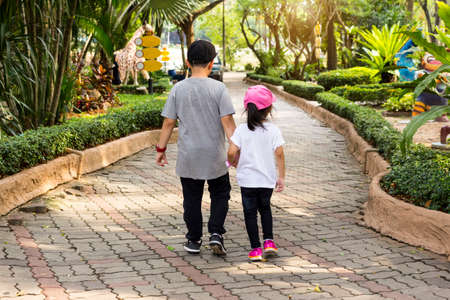 portrait of two kids brother and sister holding hands and walking on walkway in beautiful park
