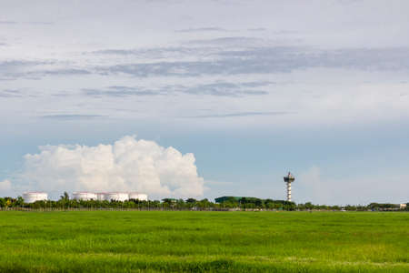 airport control tower for air traffic management with at green field near oil tank on cloudy sky background in evening Standard-Bild