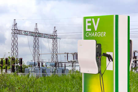 electric vehicle charging (Ev) station and plug of power cable supply for Ev car on high voltage electric power substation background Reklamní fotografie