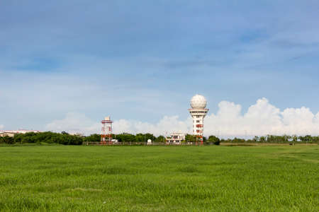weather radar at aeronautical meteorological station for information for air traffic with green field on blue sky background in bright day Foto de archivo