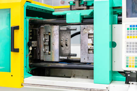 metal mould or plastic injection mold setup on high pressure injection molding machine for mass production or manufacturing in industrial and touch screen foreground