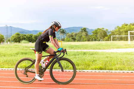 asian young woman athletes cycling on a race track intently and happily at outdoor sports field in bright day