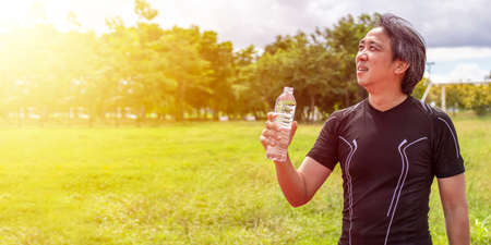 asian man in black sportswear stand and hold clean or pure water bottle for drinking after exercise or running at outdoor sport field with sunshine