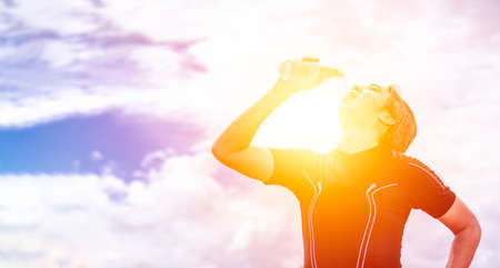 asian man in black sportswear stand and drinking clean or pure water after exercise or running at outdoor in bright day with sun and sunshine