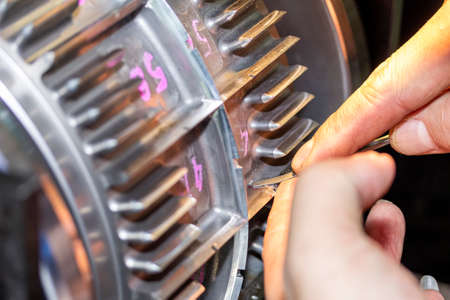 Close up hand of operator use a diamond file or equipment to polish and decorate blade of roller die cut or workpiece after welding process