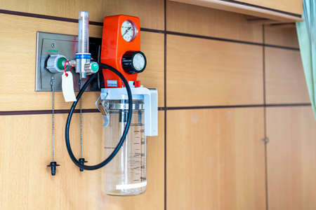 suction unit tube and storage bottle tank for mucus or waste of patient and oxygen flow regulator with tube scale for help breathing patients on wall in room at hospital