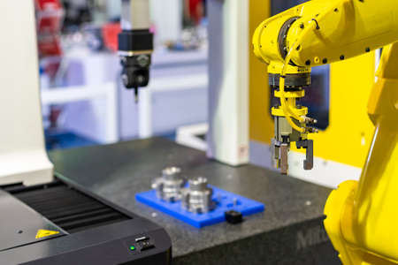high technology robot grip with automatic clamp or chuck for catch and carry engine part or automobile part transfer to coordinate measurement machine (CMM) for inspection Stock Photo