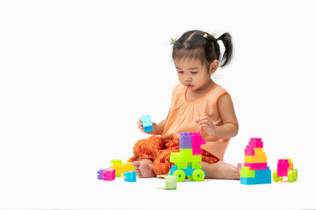 Asian child girl in Thai traditional dress sit and play colorful plastic blocks or toy happily isolated on white background