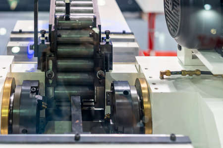 Cylindrical steel workpiece or pipe It is arranged in a automatic conveyor rail sent to a lathe machine for forming in production line at factory Stock Photo
