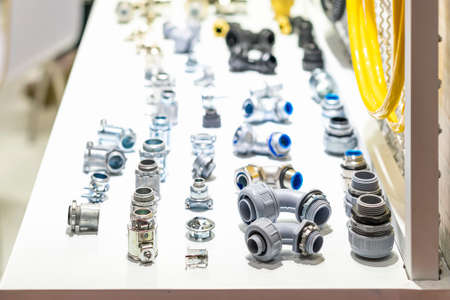 Plastic pvc and metal pipe connector conduit such as thread socket union fitting elbow liquidlight flexible etc for plumbing or electric wiring pipe work on table Archivio Fotografico