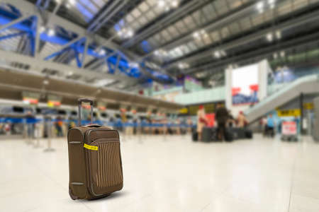 Brown color trolley travel bag or luggage at international airport front of check in counter