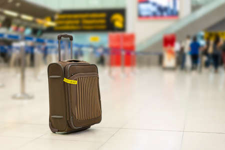 Brown color trolley travel bag or luggage at international airport hall near check in counter