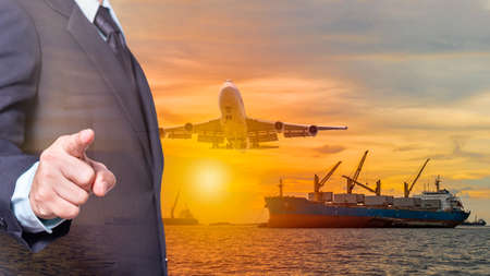 business man wearing a suit point finger forward on image air plane fly over huge cargo ship sailing in the sea in evening with sunset background point focus at finger