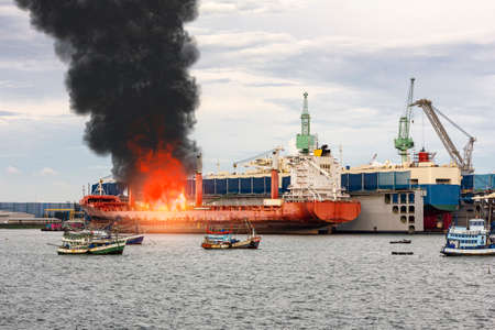 Large general cargo ship for logistic import export goods and other the explosion and had a lot of fire and smoke while moored at harbor in afternoon