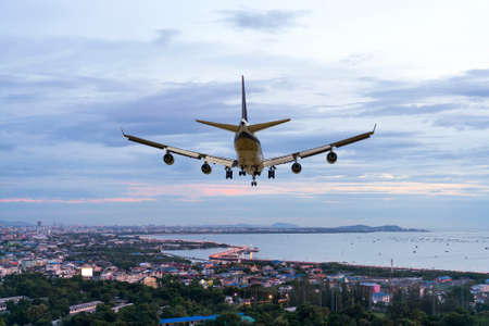 rear image commercial passenger aircraft or cargo airplane fly over bridge coastal road and city or town near cost of sea in evening