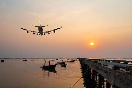 rear image commercial passenger aircraft or cargo airplane fly over fishing wood boat floating in the sea at jetty in evening with golden sunset seascape view