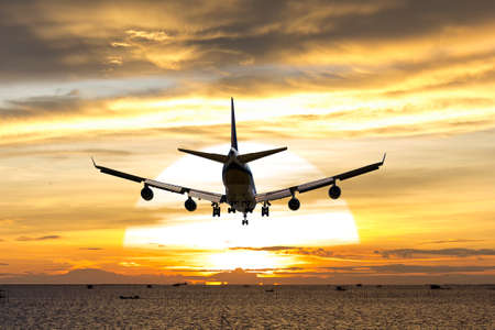 rear image commercial passenger aircraft or cargo transportation airplane fly over coast of sea after takeoff from airport in evening with sun and golden sunset seascape view