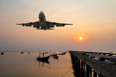 front image commercial passenger aircraft or cargo airplane fly over fishing wood boat floating in the sea at jetty in evening with golden sunset seascape view