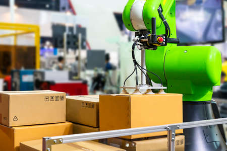 Close up precision robot arm and automatic vacuum or suction cup for pick - place transport paper box or various material sheet plate goods product of manufacturing process in industrial Foto de archivo