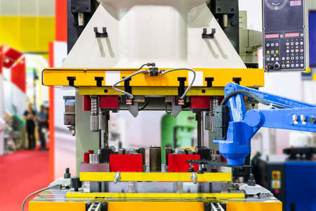 Automatic hydraulic press stamping machine with press mold or die fixture for metal sheet forming in manufacturing process in industrial with robot arm and suction cup Foto de archivo