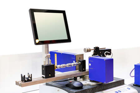 Machine workpiece or automotive part shaft during inspection or measuring dimension by precision laser system unit with screen monitor in industrial work isolated with clipping path