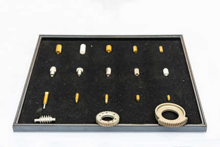Various mini metal gear parts such as helical and worm screw or spiral gear in box Foto de archivo