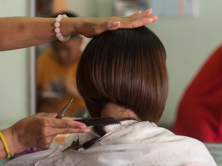 hair stylist: Hair stylist trimming short hair young asian woman at beauty salon.