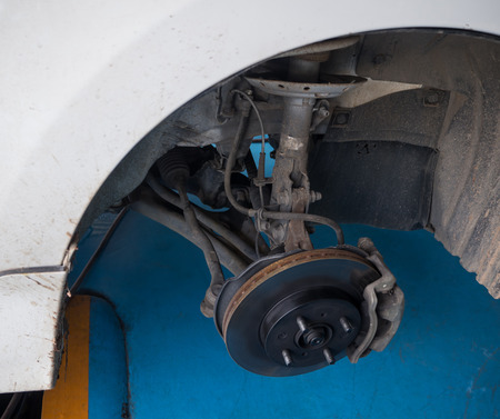 brake caliper: Front wheel disk brake and caliper maintenance job in progress. Stock Photo