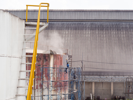 Worker cleaning storage tank by air pressure sand blasting in high position. Stock Photo