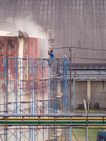 air pressure: Worker cleaning storage tank by air pressure sand blasting in high position. Stock Photo