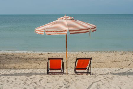 Chairs with umbrella on beach at Chao Lao Beach, Thailand.