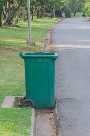 Large green wheelie bin at public park.