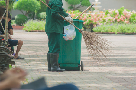 Cleaning staff collect garbage to large green wheelie bin in public park.