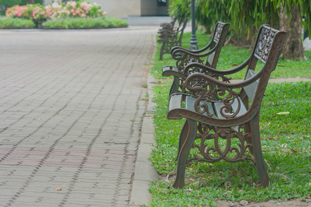 antique furniture: Metal steel old fashioned bench chair on green grass in public park.