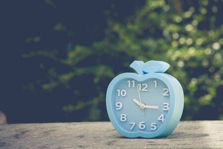 Time Management Concept : Blue alarm clock on concrete floor with green leaves background. (Autumn filter effect)