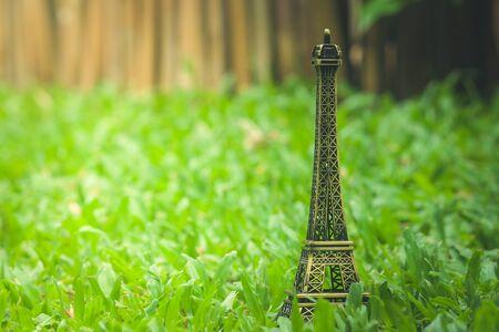 Vacation Concept : Little model of Eiffel tower on green grass in garden. (Autumn filter effect)