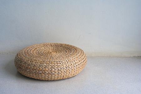 Round brown wicker chair in vintage style on cement floor in white room with natural light. Stock fotó