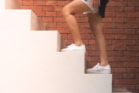 Business Success Concept : Woman is walking up white concrete stairs outside in the buildings with orange brick background. (Autumn filter effect)