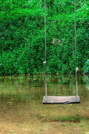 play the old park: Wooden swing hanging on tree above the water stream at outside resort. (Autumn filter effect)