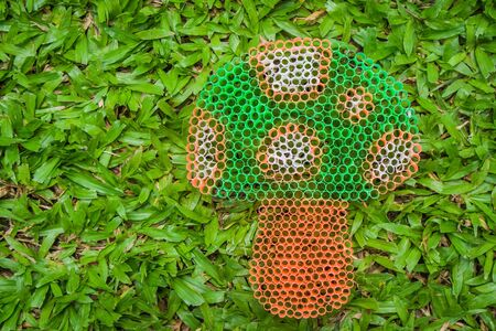 polymer: Close up colorful mushroom on green grass handmade with plastic straw.