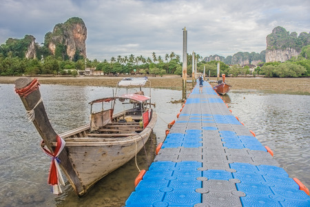 Traditional long tail boat on Railay Beach with walkway to harbor and view of green island, Krabi Provine, Thailand. (HDR filter effect) Stok Fotoğraf