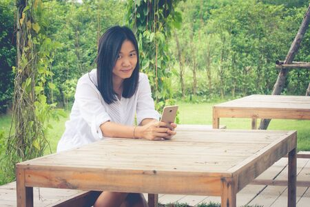 Asian woman sitting on wooden chair at outdoor garden and playing her smartphone. (Autumn filter effect)
