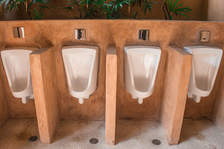 Row of outdoor white urinals men in public toilet. (Vintage filter effect)