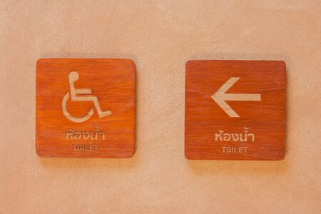 Cripple toilet signs on wooden board with arrow pointing way on clay wall in vintage style. Stok Fotoğraf - 81707218