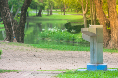 Drinking fountain in the park with green natural and sunlight background. Stok Fotoğraf